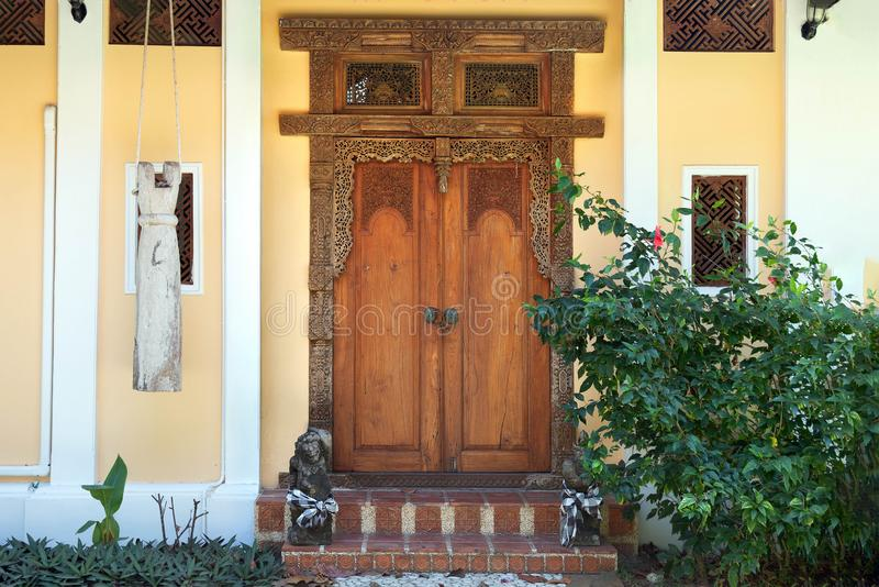 Entrance to the yellow house with old wooden windows and door with carved patterns. Stone path leading to the stairs stock photos