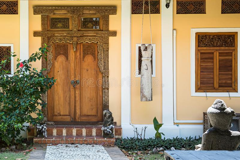 Entrance to the yellow house with window. Old wooden door with carved patterns. Stone path leading to a locked door royalty free stock image