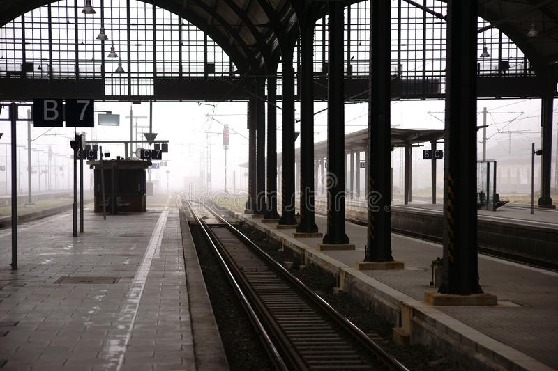Platform in the fog. The entrance of a train station in the fog with railroad tracks and platforms royalty free stock photography