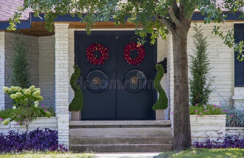 Entrance of an upscale white stone house with Asian style doors with large round handles and red wreaths and attractive landscapin royalty free stock photo