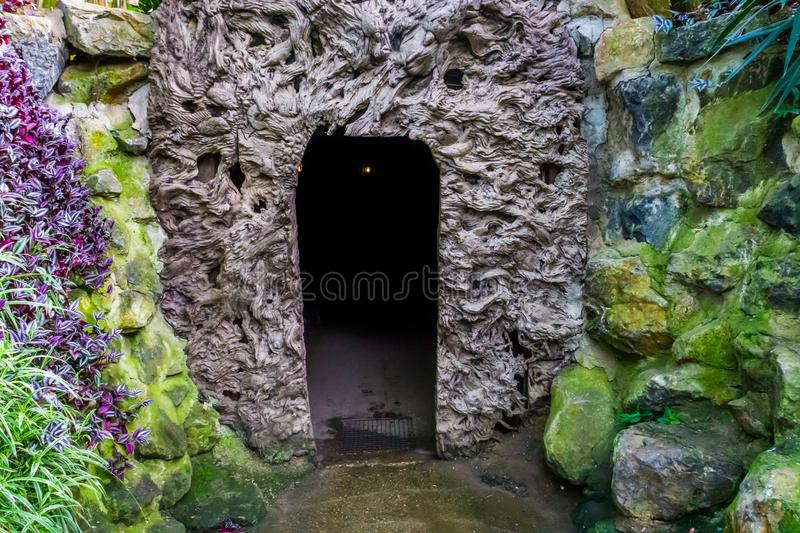 Entrance of a very dark cave, halloween haunted den concept, scary scenery royalty free stock photography