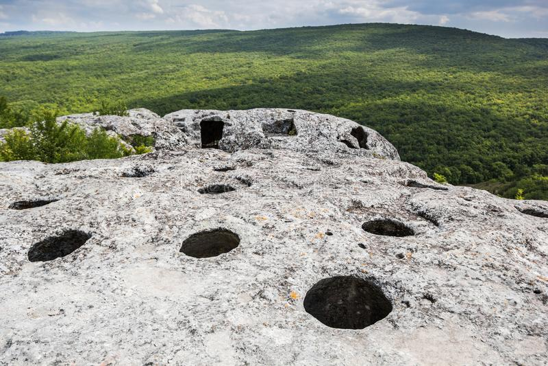 Entrata alla caverna sopra la montagna, vista della foresta e la valle fotografia stock libera da diritti