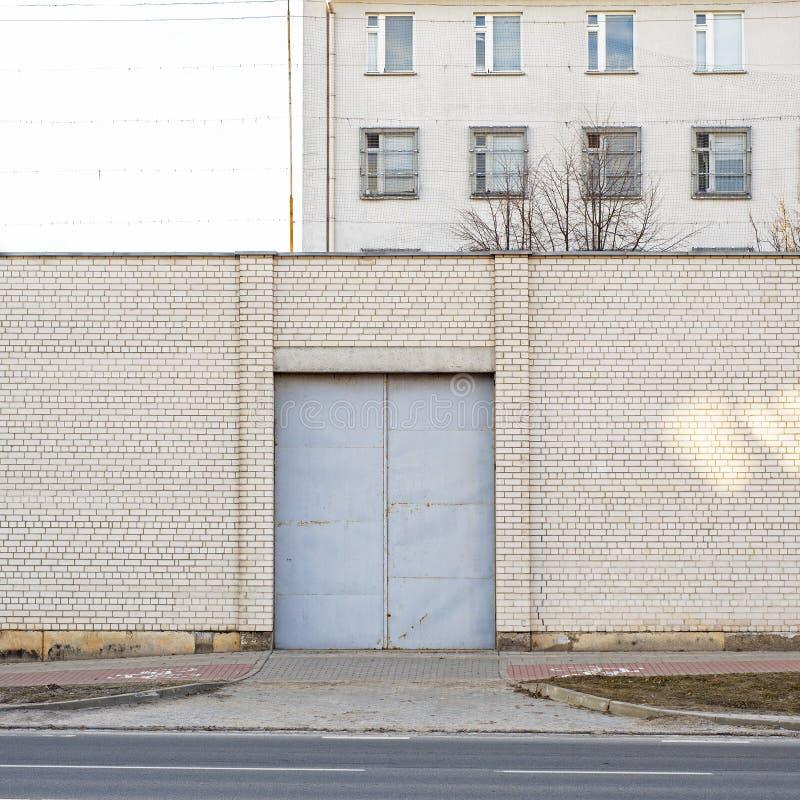 Entrata a costruzione abbandonata circondata dal grande muro di mattoni bianco immagini stock libere da diritti