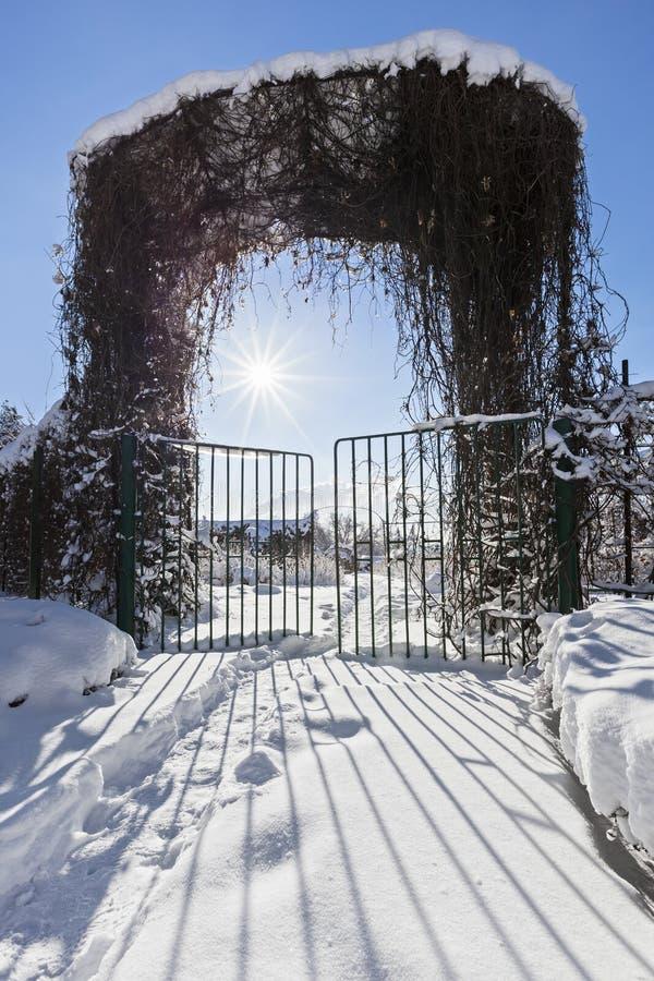 Entrata del giardino di inverno con il portone a solidificazione rapida, il sole luminoso e il beauti fotografia stock libera da diritti