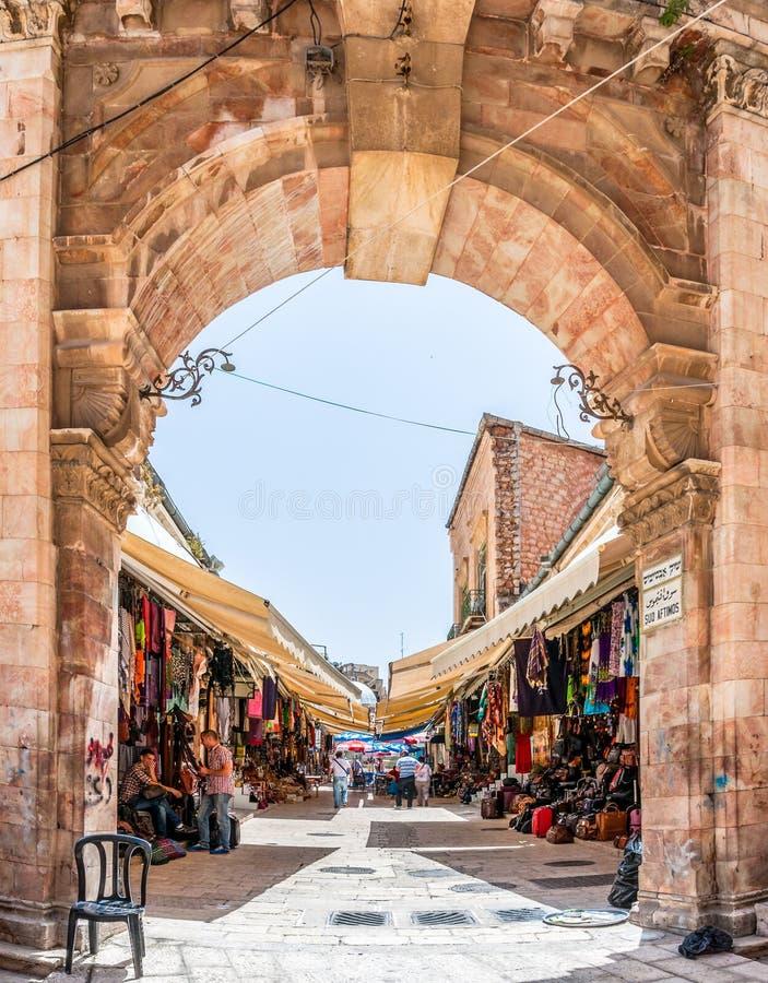 Entrata dell'arco ad uno di molti vicoli nel mercato antico di Città Vecchia di Gerusalemme pieno dei negozi con tutti i tipi di  fotografia stock libera da diritti