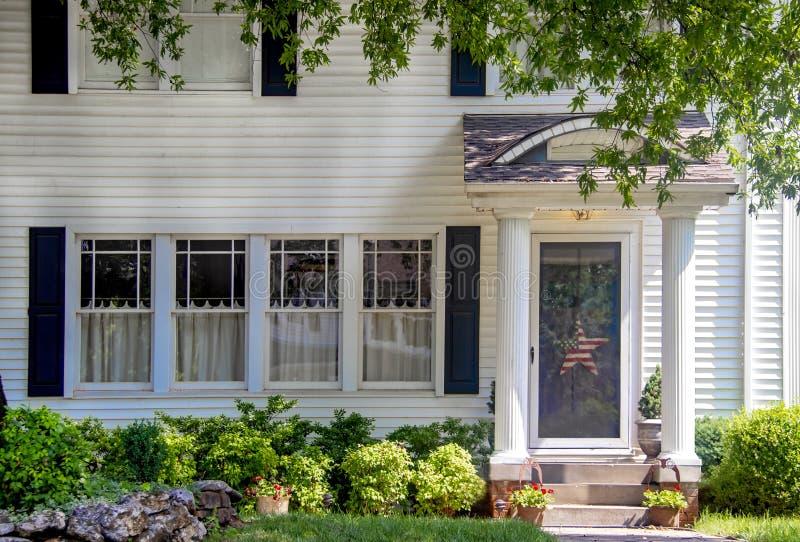 Entrata della casa di legno bianca affascinante con le colonne sul portico e bei rami d'abbellimento e sporgentesi e un bianco ro fotografia stock libera da diritti