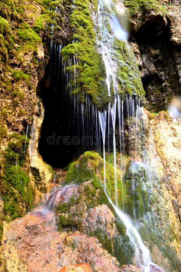 Entrata della caverna nascosta dietro una piccola cascata La stalattite frana le montagne del Caucaso del nord, Russia fotografia stock libera da diritti