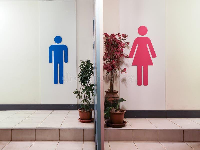 Entrata della toilette con il segno della toilette con il simbolo blu dell'uomo della siluetta ed il simbolo rosso della donna de immagine stock libera da diritti