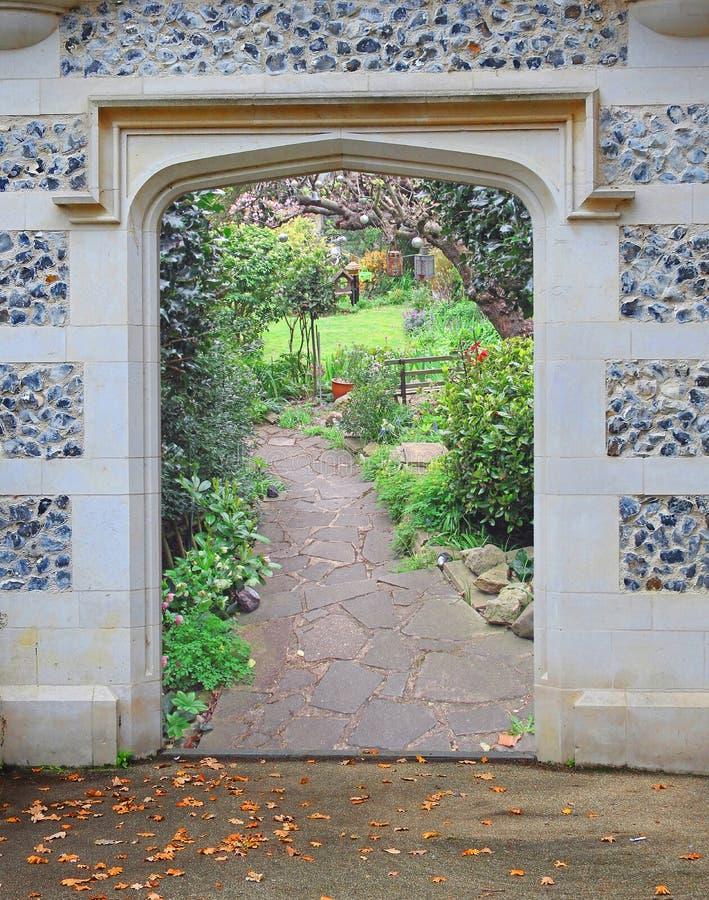 Entrata di pietra della porta dell'ingresso dell'arco alle belle piante dei fiori del giardino fotografie stock