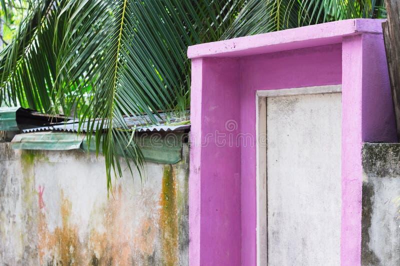 Entrata di una casa rosa con una porta di legno bianca immagini stock libere da diritti