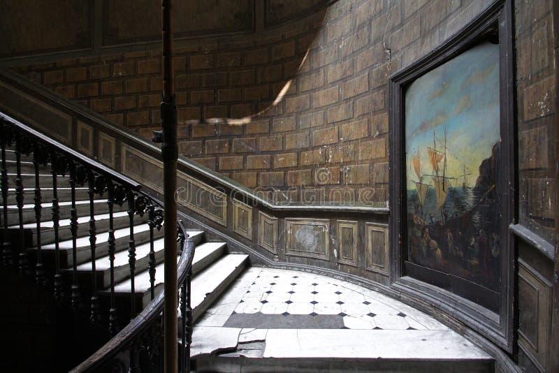 Entrata di vecchia casa del diciannovesimo secolo con pittura su una parete e su una scala d'annata fotografia stock libera da diritti
