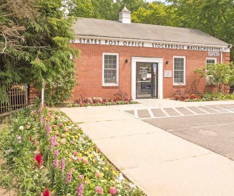 Entrata e marciapiede della costruzione dell'ufficio postale degli Stati Uniti con il giardino floreale immagine stock