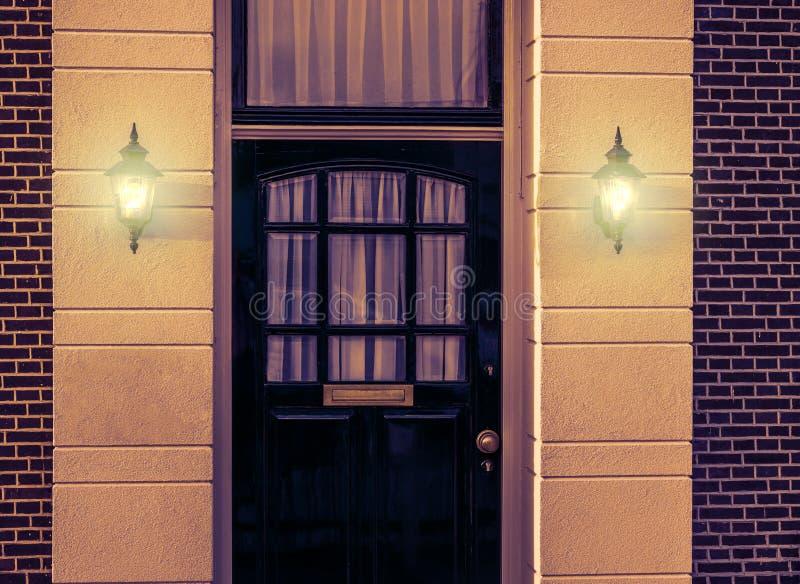 Entrata principale di legno con le lanterne accese della parete che splendono luce nell'architettura scura e olandese di notte immagini stock