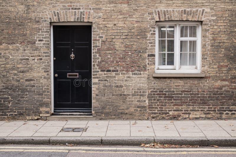 Entrata principale nera su un muro di mattoni ristabilito di un edificio residenziale della casa vittoriana immagini stock libere da diritti