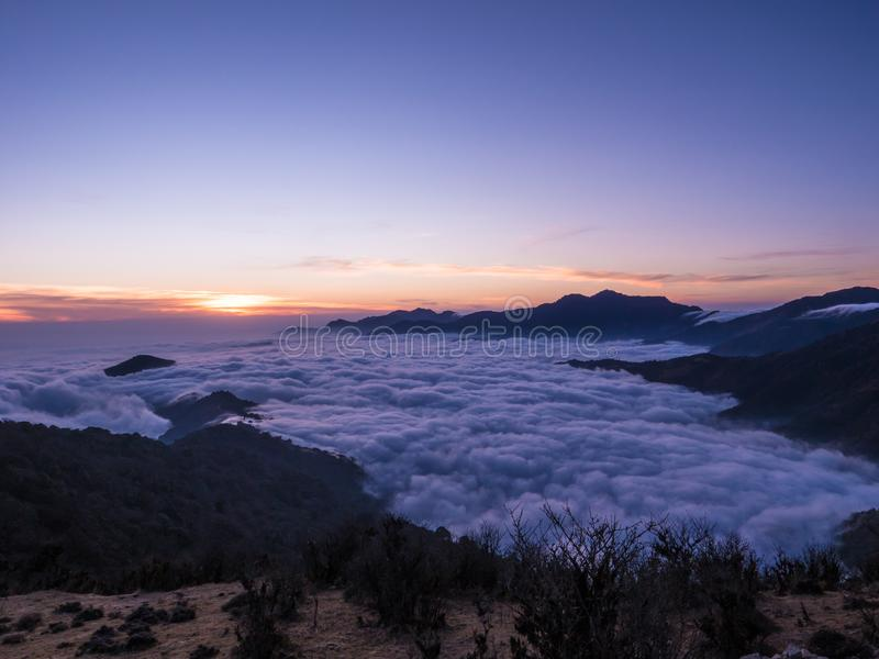 Entre as nuvens sobre o sunsetime das montanhas foto de stock