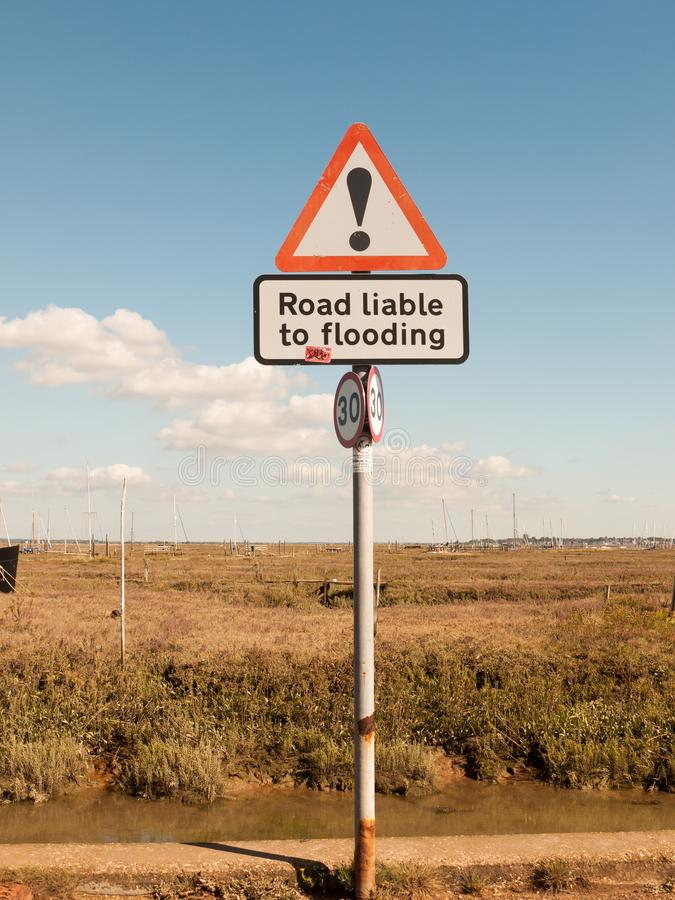Entre a estrada vermelha da exclamação do triângulo do sinal de estrada responsável à inundação foto de stock royalty free