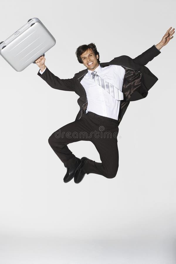 Entre le ciel et la terre de sourire de With Briefcase Jumping d'homme d'affaires photographie stock libre de droits