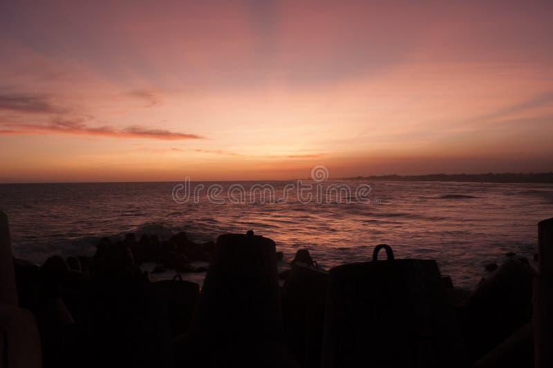 Entre o por do sol e a praia de Glagah dos quebra-mares, Yogyakarta, Indonésia fotografia de stock royalty free