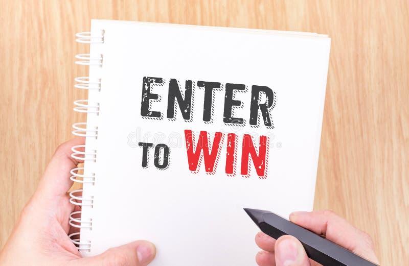 Entre para ganhar a palavra no caderno branco da pasta de anel com holdin da mão fotos de stock royalty free