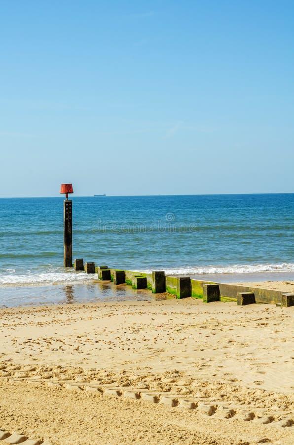 Entre pilhas em um Sandy Beach, em um oceano azul e em uma areia amarela, ensolarados imagem de stock