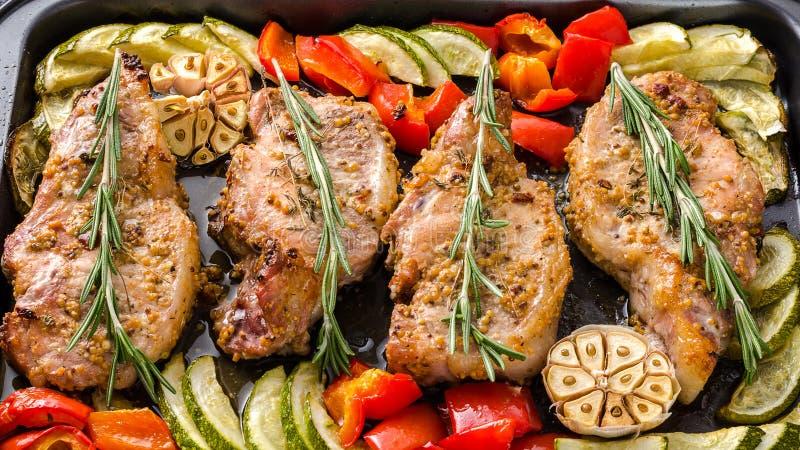 Entrecôtes de porc cuites au four par four avec le paprika et la courgette photos libres de droits