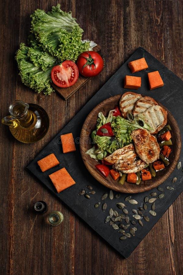 Entrecôte arrostito del palo del manzo del taglio con le verdure, il pane e le specie sui precedenti di legno dello scrittorio fotografia stock