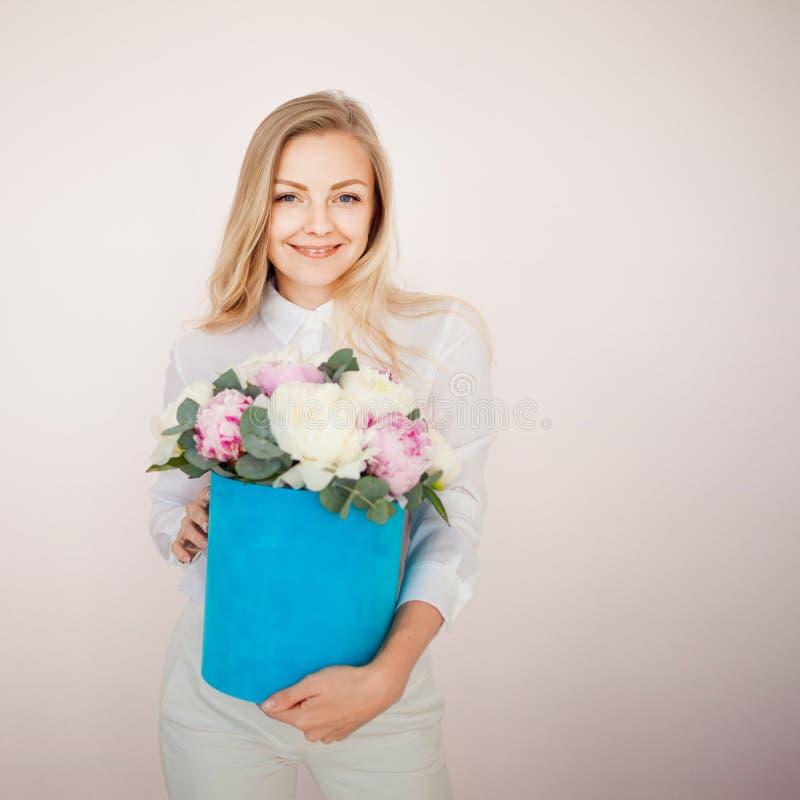 Entrega à moda da flor, presente Mulher com flores em uma caixa do chapéu Ramalhete dos peonies fotografia de stock royalty free
