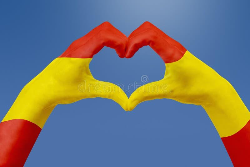 Entrega a bandeira da Espanha, dão forma a um coração Conceito do símbolo do país, no céu azul ilustração stock