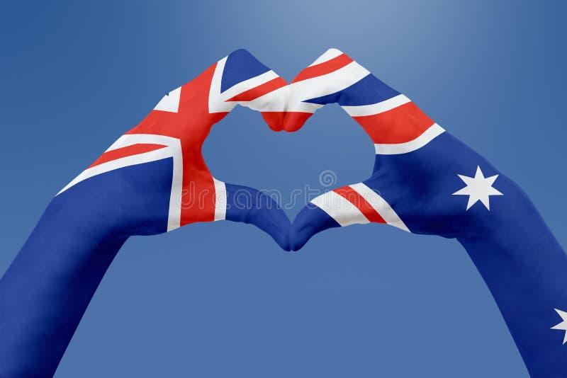 Entrega a bandeira de Austrália, dão forma a um coração Conceito do símbolo do país, no céu azul imagens de stock