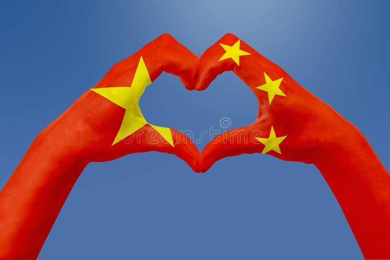 Entrega a bandeira de China, dão forma a um coração Conceito do símbolo do país, no céu azul ilustração do vetor