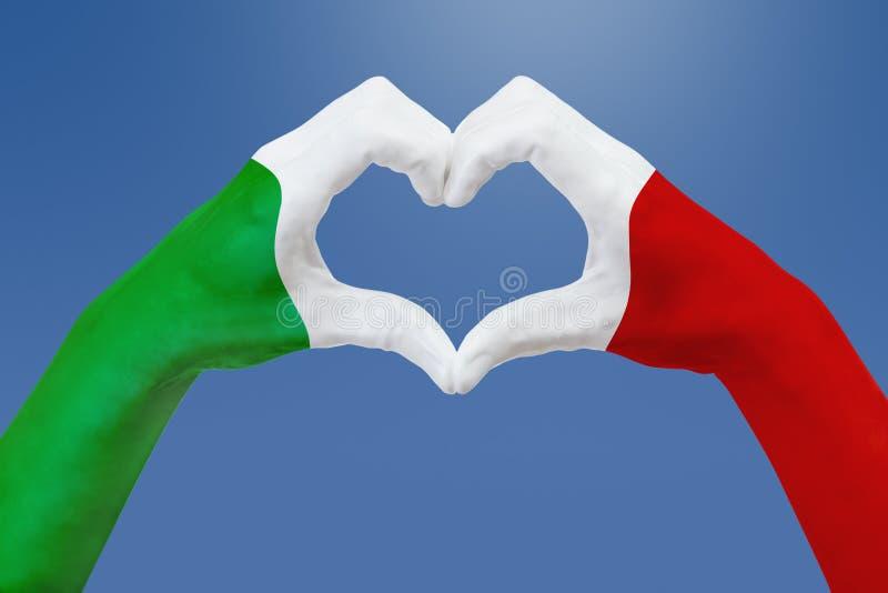 Entrega a bandeira de Itália, dão forma a um coração Conceito do símbolo do país, no céu azul ilustração royalty free