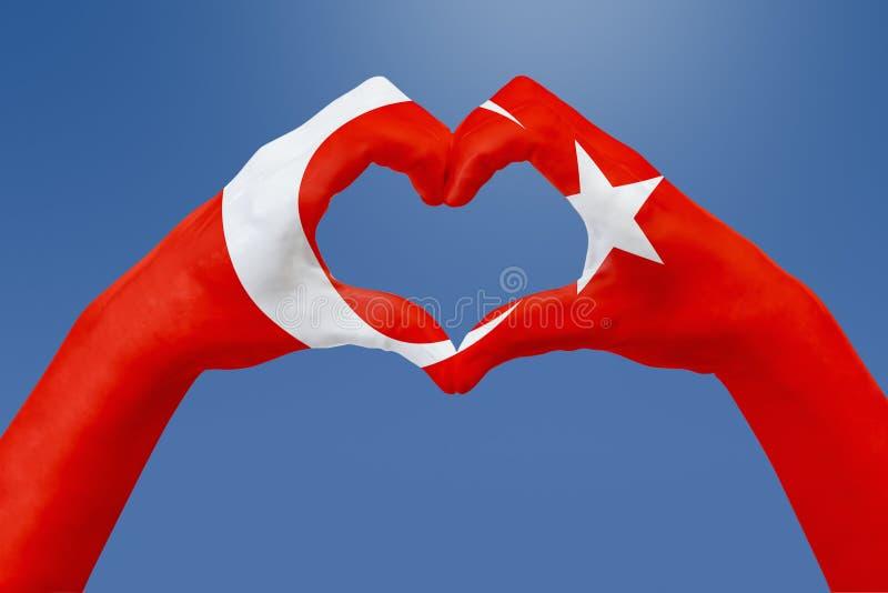 Entrega a bandeira de Turquia, dão forma a um coração Conceito do símbolo do país, no céu azul ilustração royalty free