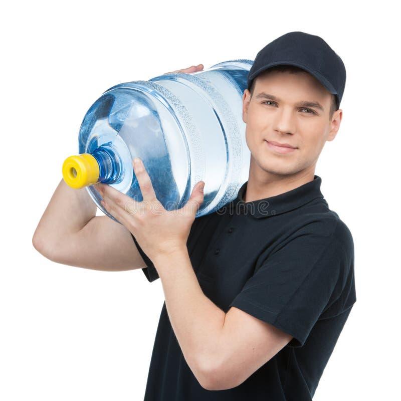 Entrega da água. Entregador novo alegre que guardara um jarro de água w fotografia de stock royalty free