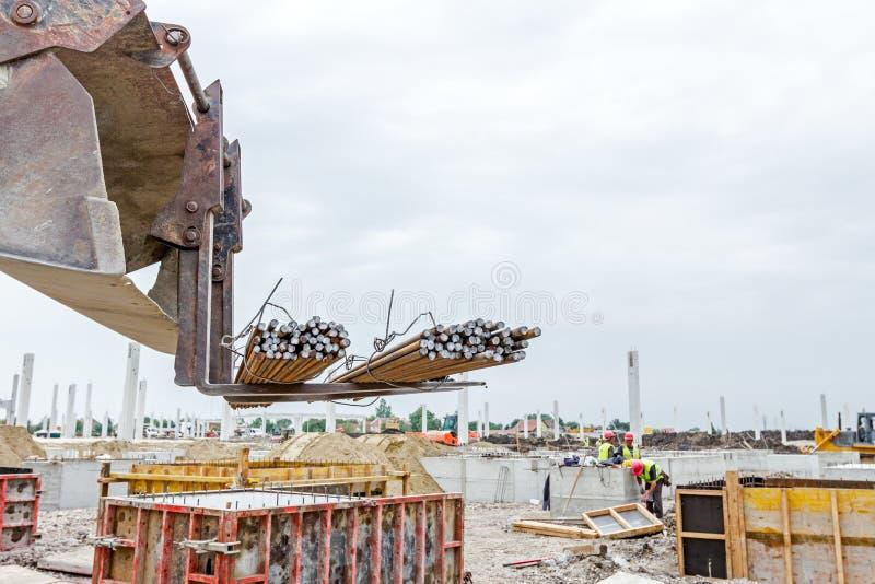 Entrega da haste da armadura no terreno de construção Conceito da logística foto de stock