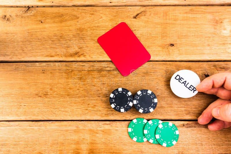 Entrega de la marca del distribuidor en fondo de madera, concesionario y jugador, concepto de póquer imagen de archivo