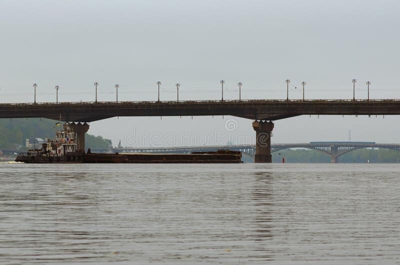 Entrega del cargo por transporte de río El barco del tirón que remolca una gabarra con la arena Puente de Paton y puente del metr fotos de archivo libres de regalías