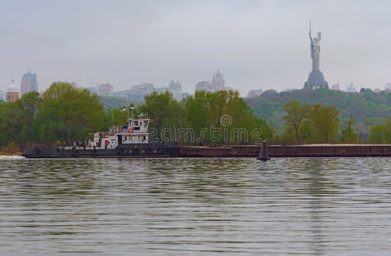 Entrega del cargo por transporte de r?o El barco del tir?n que remolca una gabarra con la arena El monumento de la patria en el f fotos de archivo