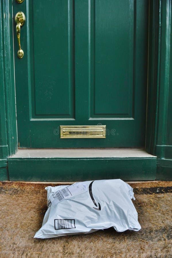 Entrega del paquete del envío del Amazonas al umbral residencial de la casa imagenes de archivo