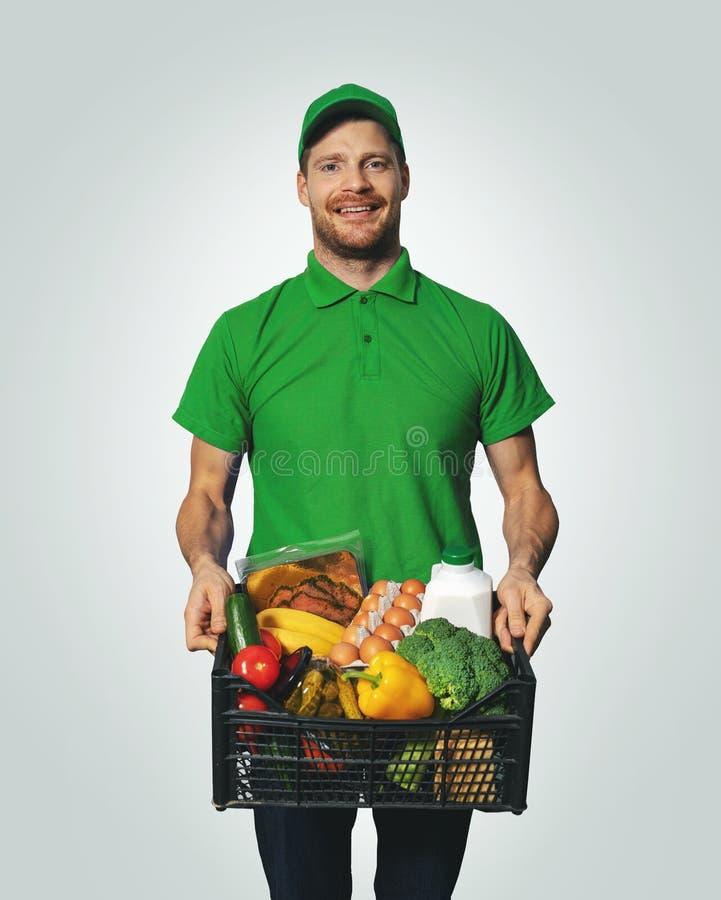 Entrega dos mantimentos - homem no uniforme verde com caixa do alimento imagem de stock royalty free