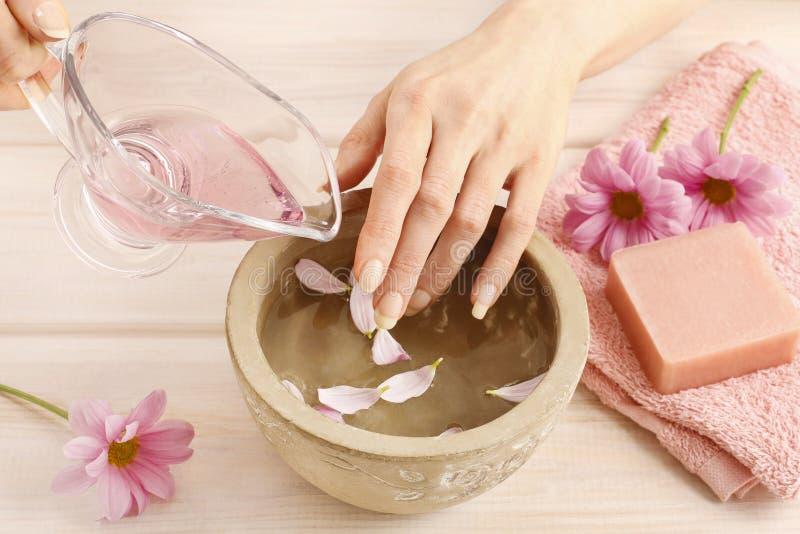 Entrega el cuenco de cerámica con agua y los aceites esenciales fotografía de archivo libre de regalías