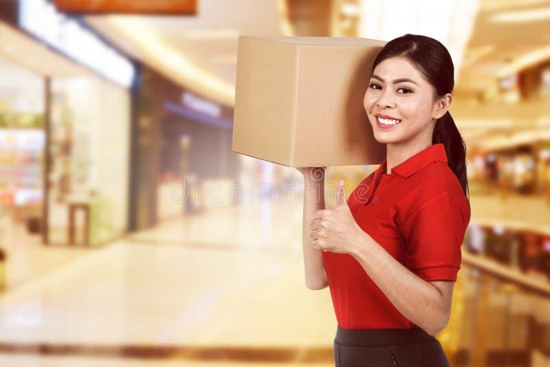 Entrega femenina asiática hermosa que lleva a cabo el paquete fotografía de archivo