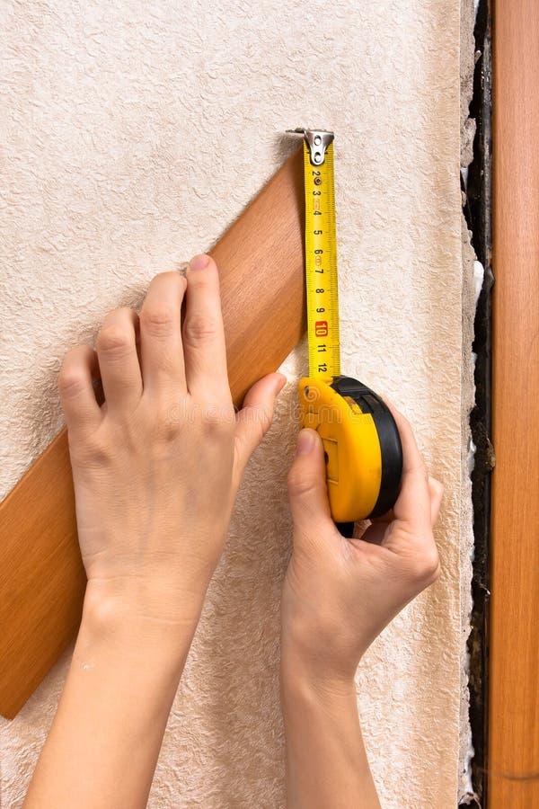 Entrega a largura de medição do platband com fita métrica fotografia de stock