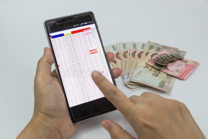Entrega a mulher que usa o smartphone com dinheiro no fundo branco fotos de stock