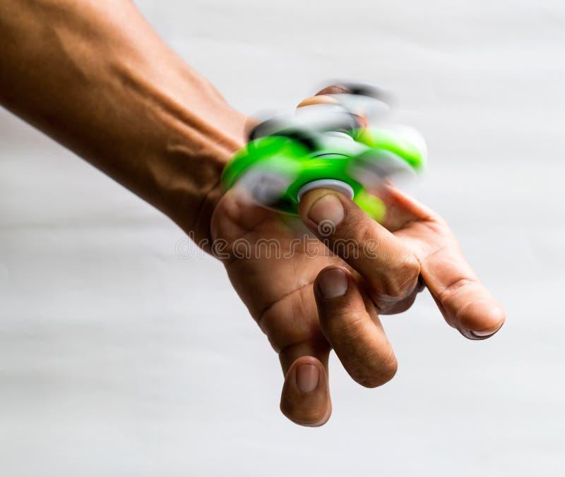 Entrega a rotação do verde do girador no dedo fotografia de stock royalty free