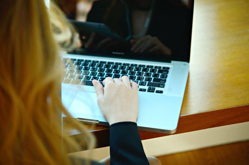 Entrega uma mulher no portátil do teclado ou o netbook que senta-se em seu DES imagem de stock