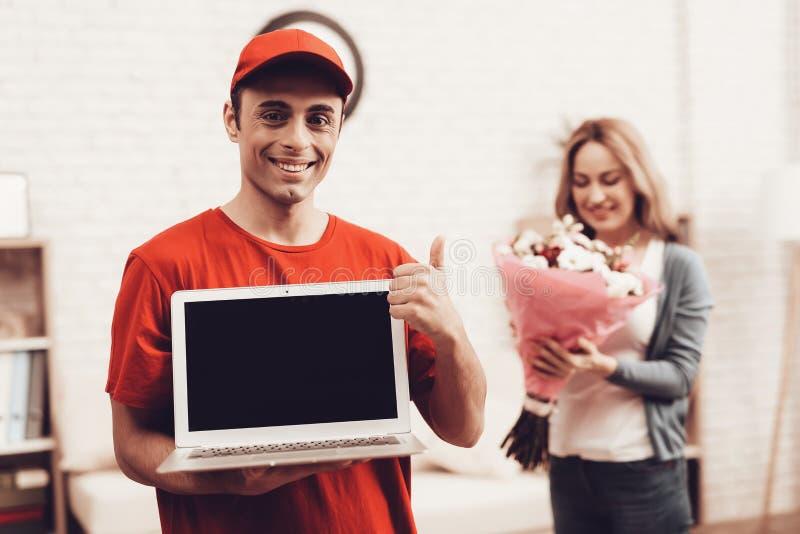 Entregador árabe com portátil e menina com flores fotografia de stock royalty free