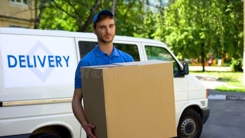 Entregador que guarda a caixa de cartão grande, transporte dos aparelhos eletrodomésticos fotografia de stock royalty free