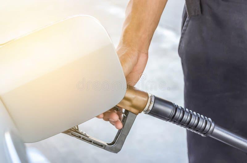 Entregue a bomba de gás do reabastecimento do bocal de combustível da posse na estação do serviço fotografia de stock royalty free