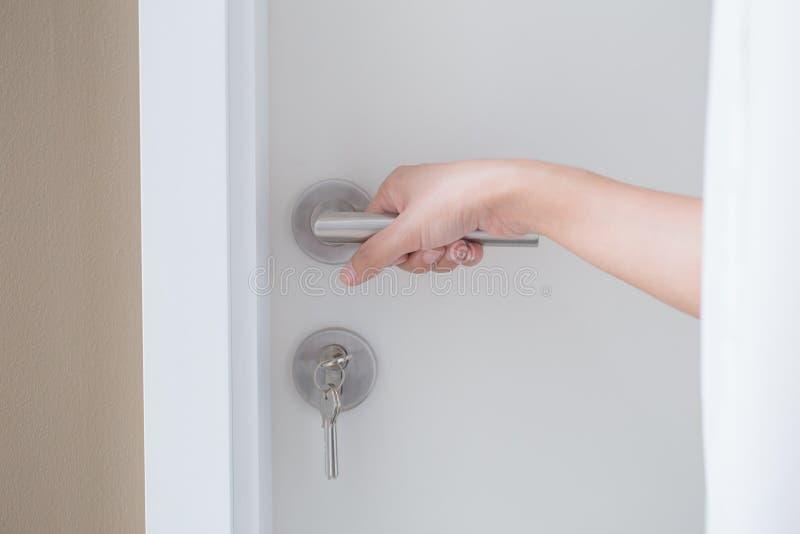 Entregue a botão de porta da posse para aberto a porta ou feche o conceito da porta fotografia de stock royalty free