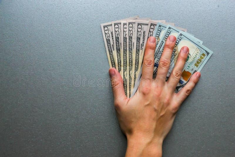 Entregue cientos y cincuenta billetes de banco del dólar imagen de archivo libre de regalías
